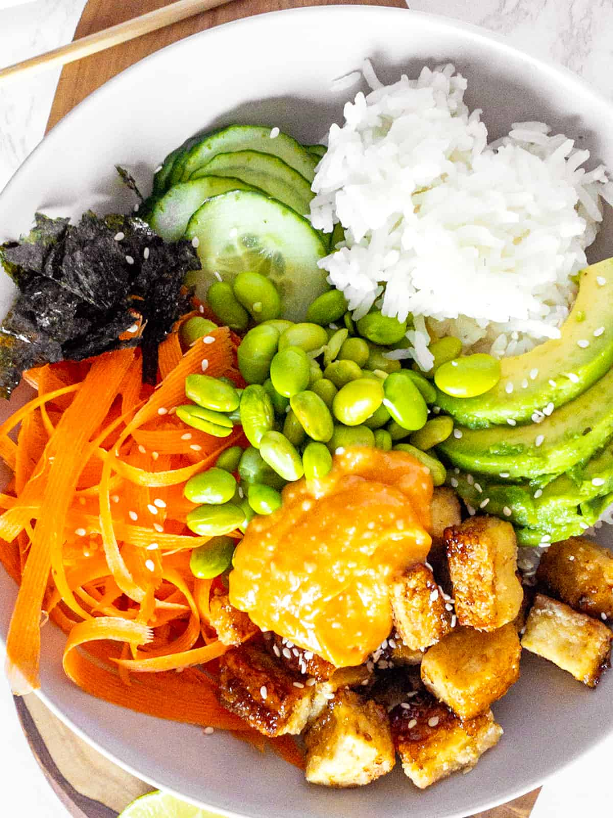 a close-up photo of a sushi bowl with tofu, carrot, cucumber, and edamame