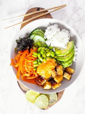 a vegan sushi bowl on a wooden cutting board with chopping sticks on the side