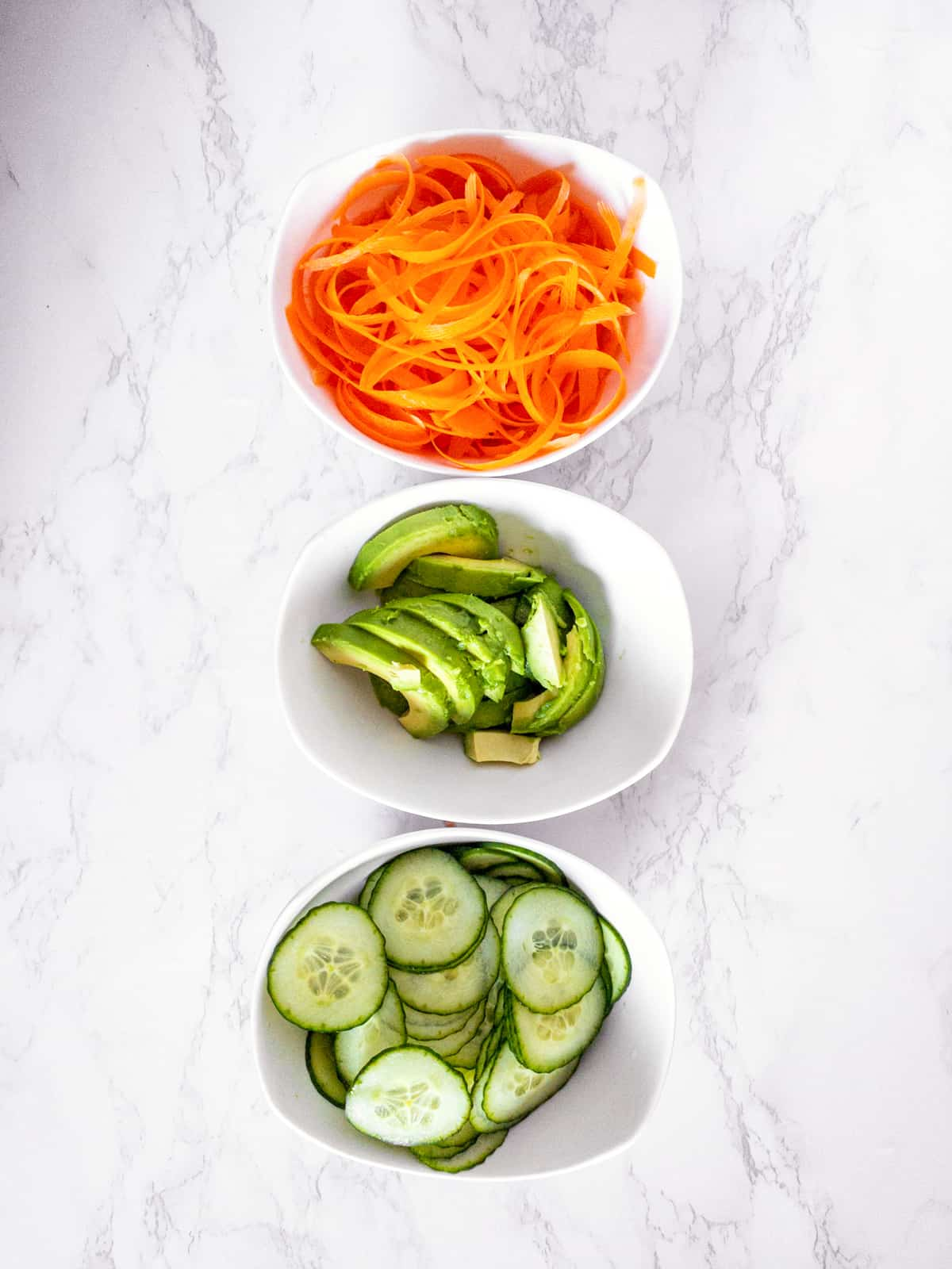 three small bowls on a marble countertop containing carrots, avocado, and cucumber