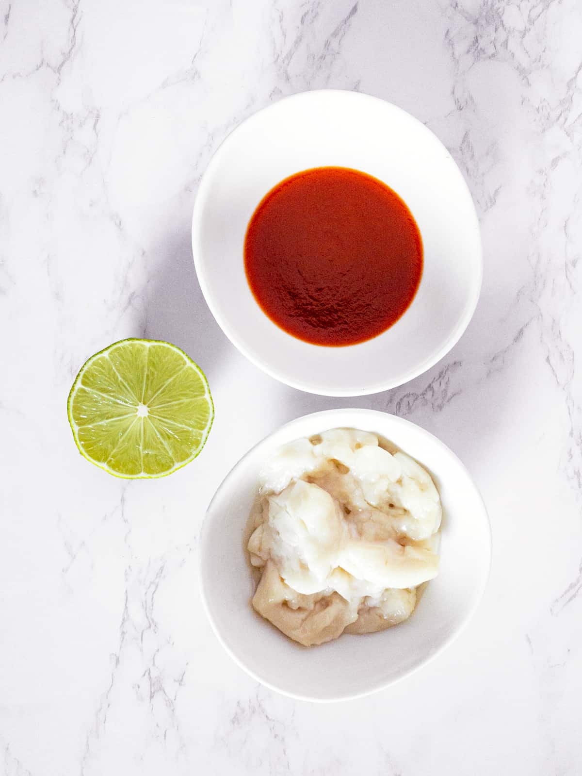 two bowls on a marble countertop containing sriracha sauce and mayonnaise