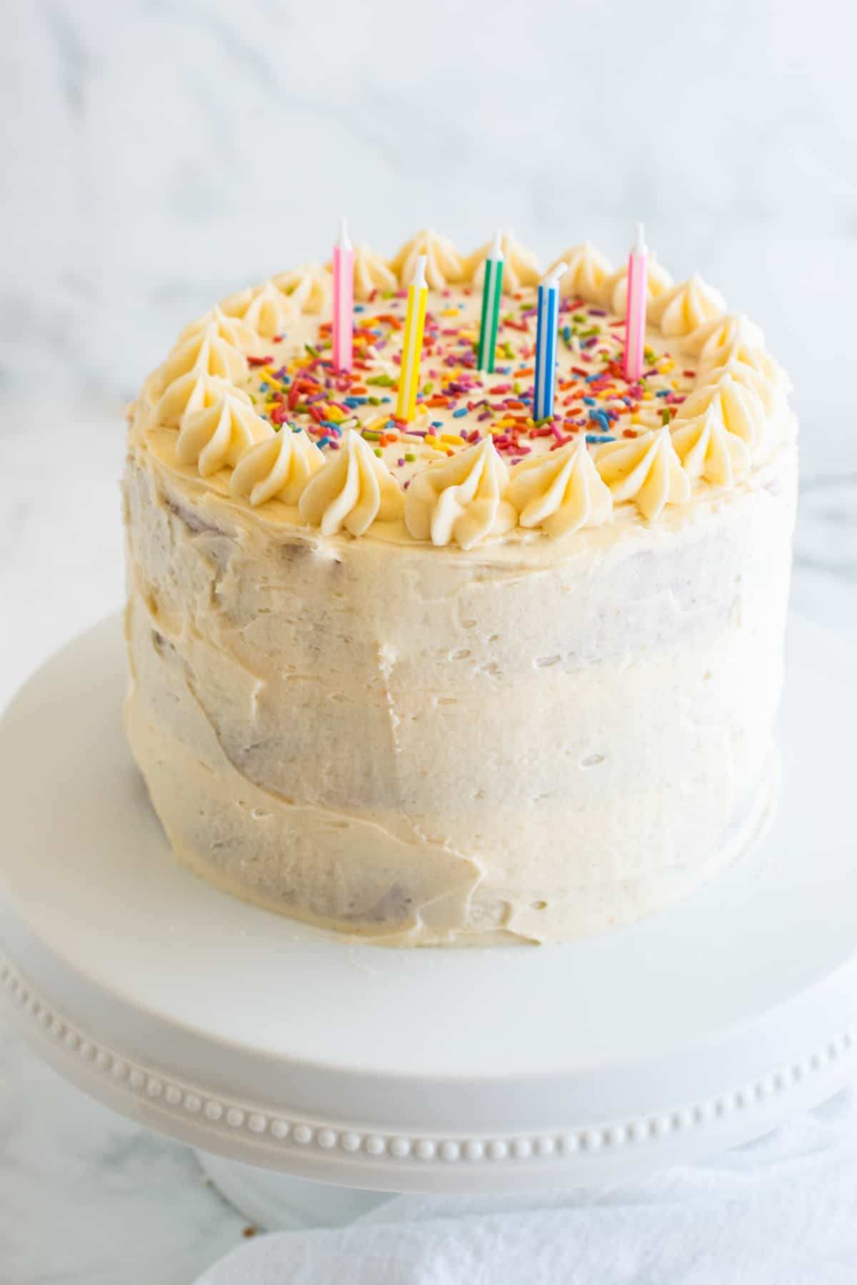 a vegan birthday cake with sprinkles and candles on a cake plate