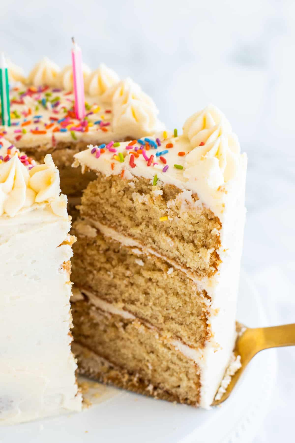 a slice of vegan vanilla cake on a cake lifter