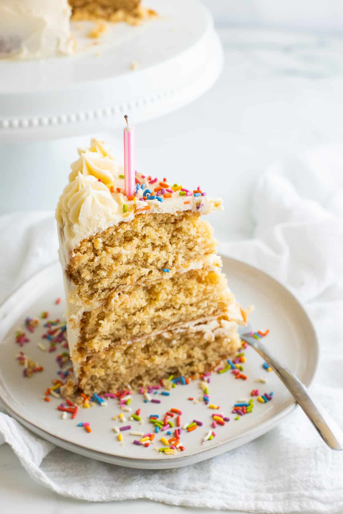a slice of vegan birthday cake with a candle and sprinkles on a beige plate