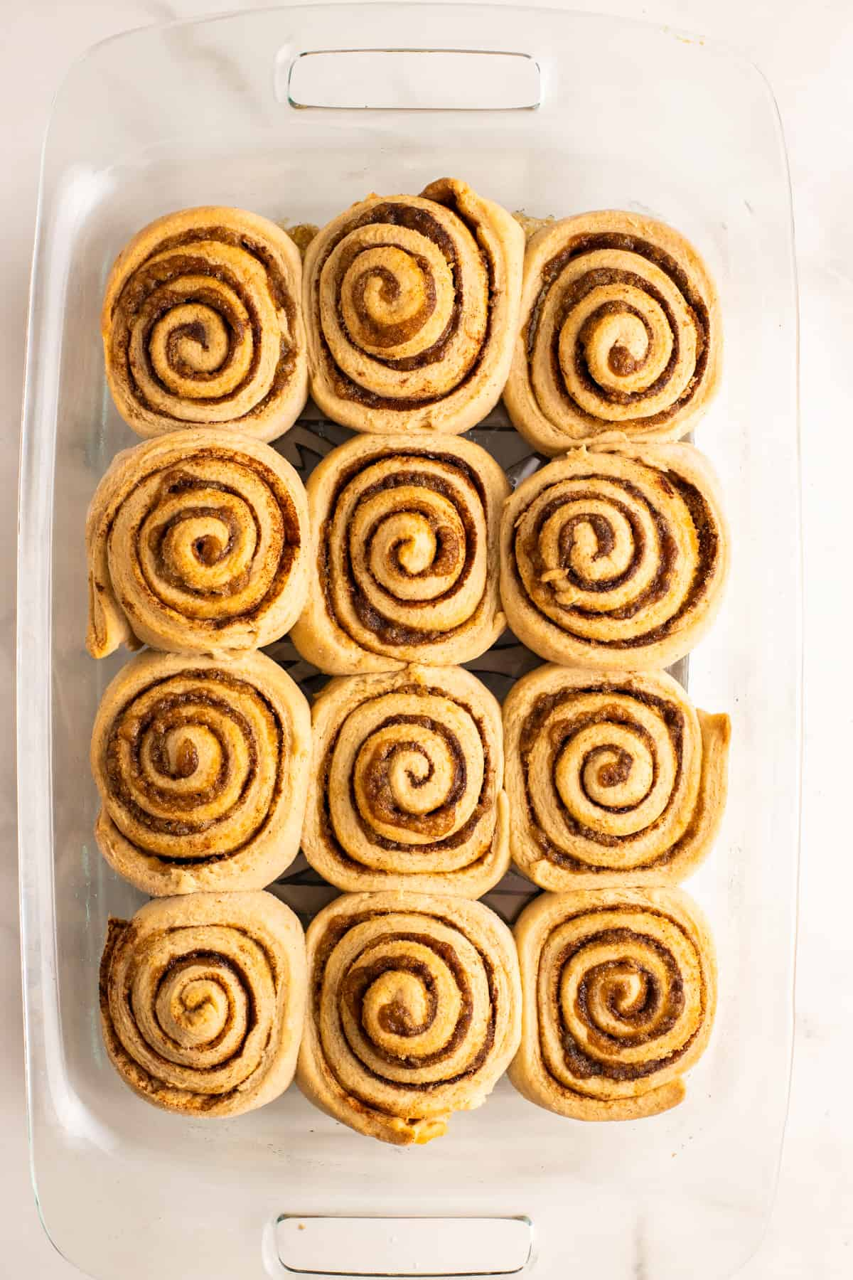 freshly baked cinnamon rolls in a glass dish on a marble countertop