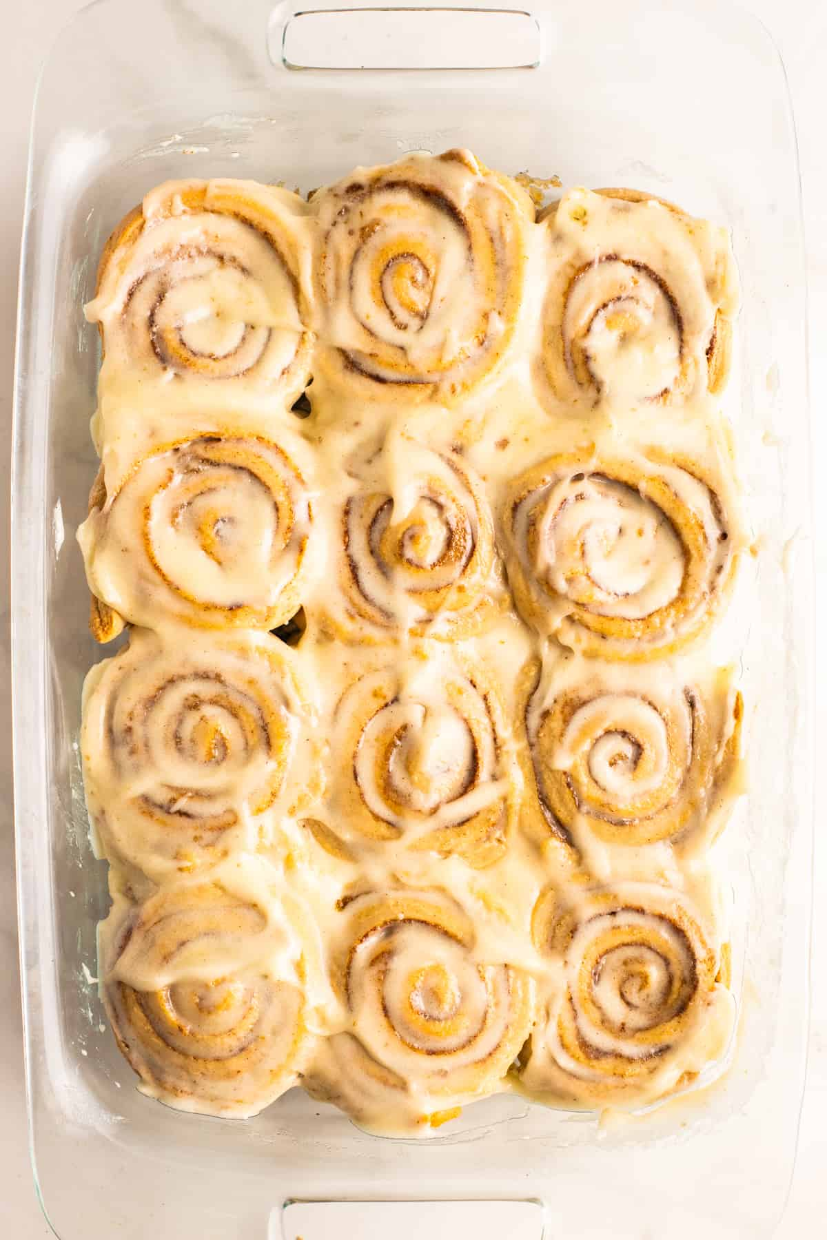 12 vegan cinnamon rolls covered with frosting in a glass dish