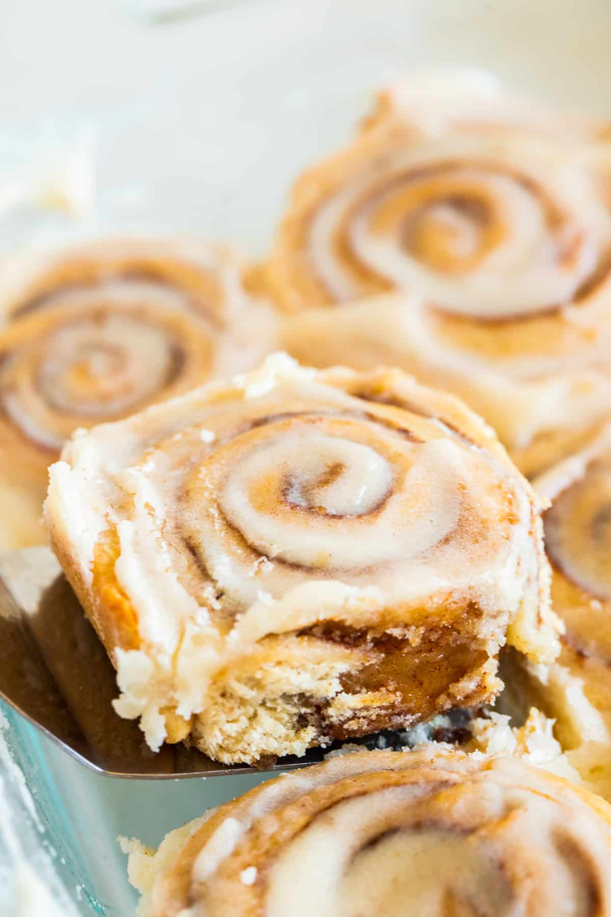 a cinnamon roll being lifted with a cake lifter