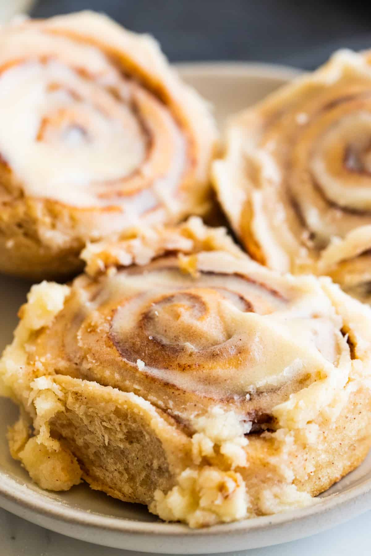 a close-up photo of three cinnamon rolls on a beige plate