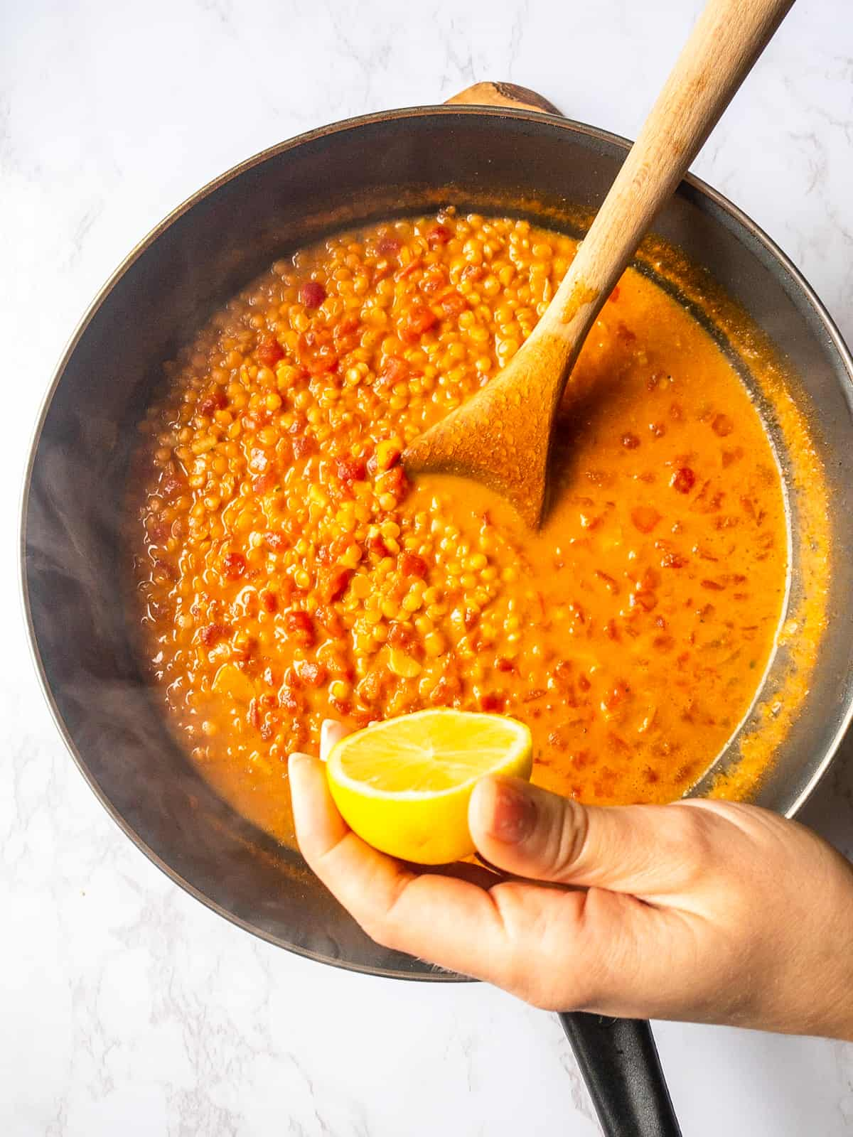 a hand squeezing a lemon over a pan with dal