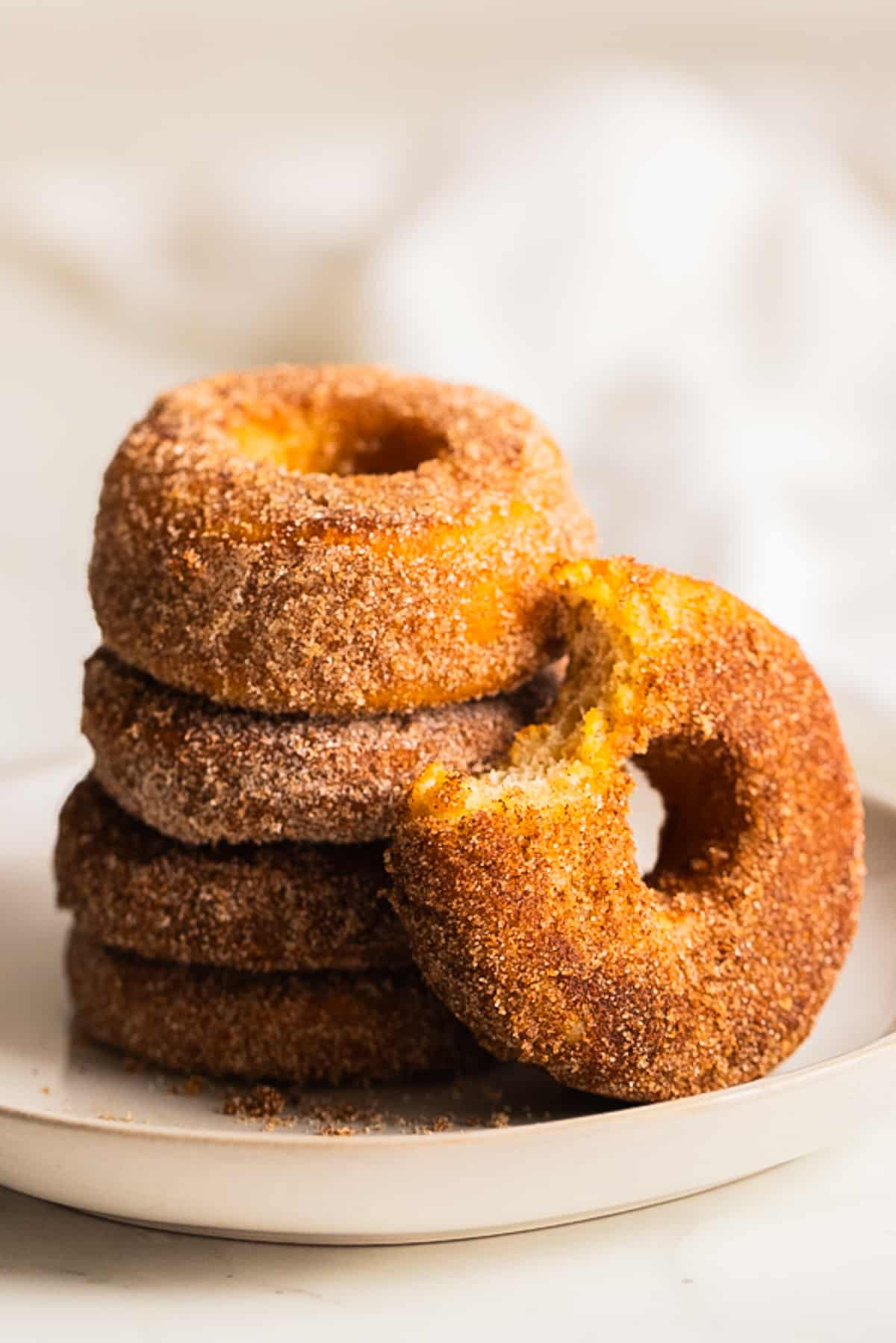 a stack of vegan donuts on a white plate