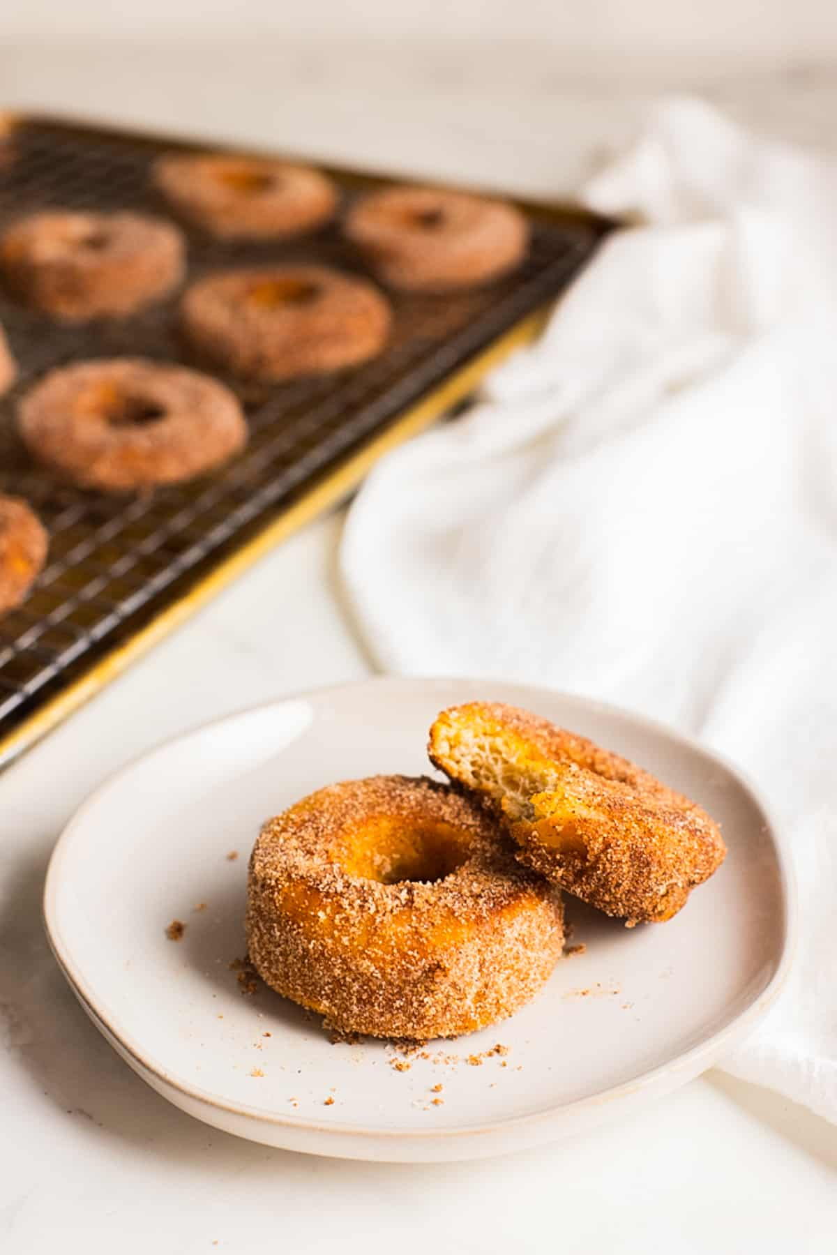 two donuts on a white plate with more donuts on a cooling rack in the background
