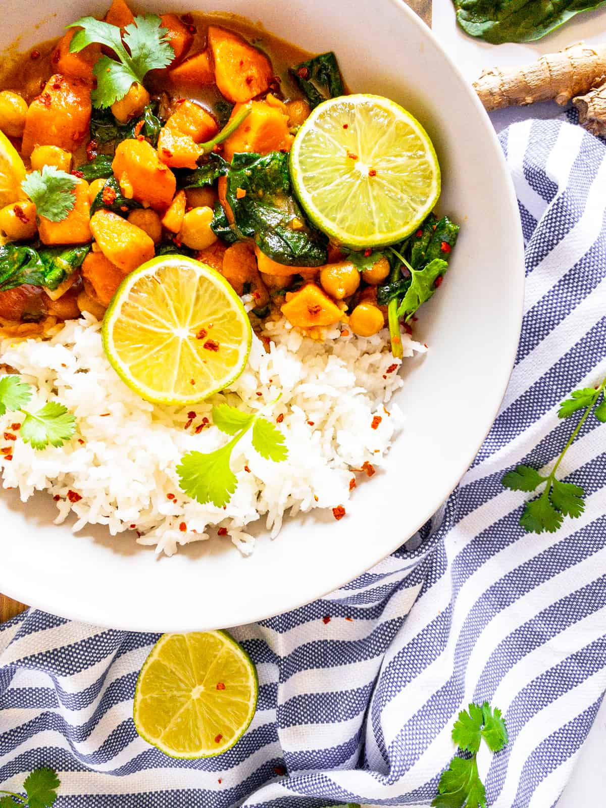 sweet potato curry with spinach and chickpeas in a white bowl with rice on the side