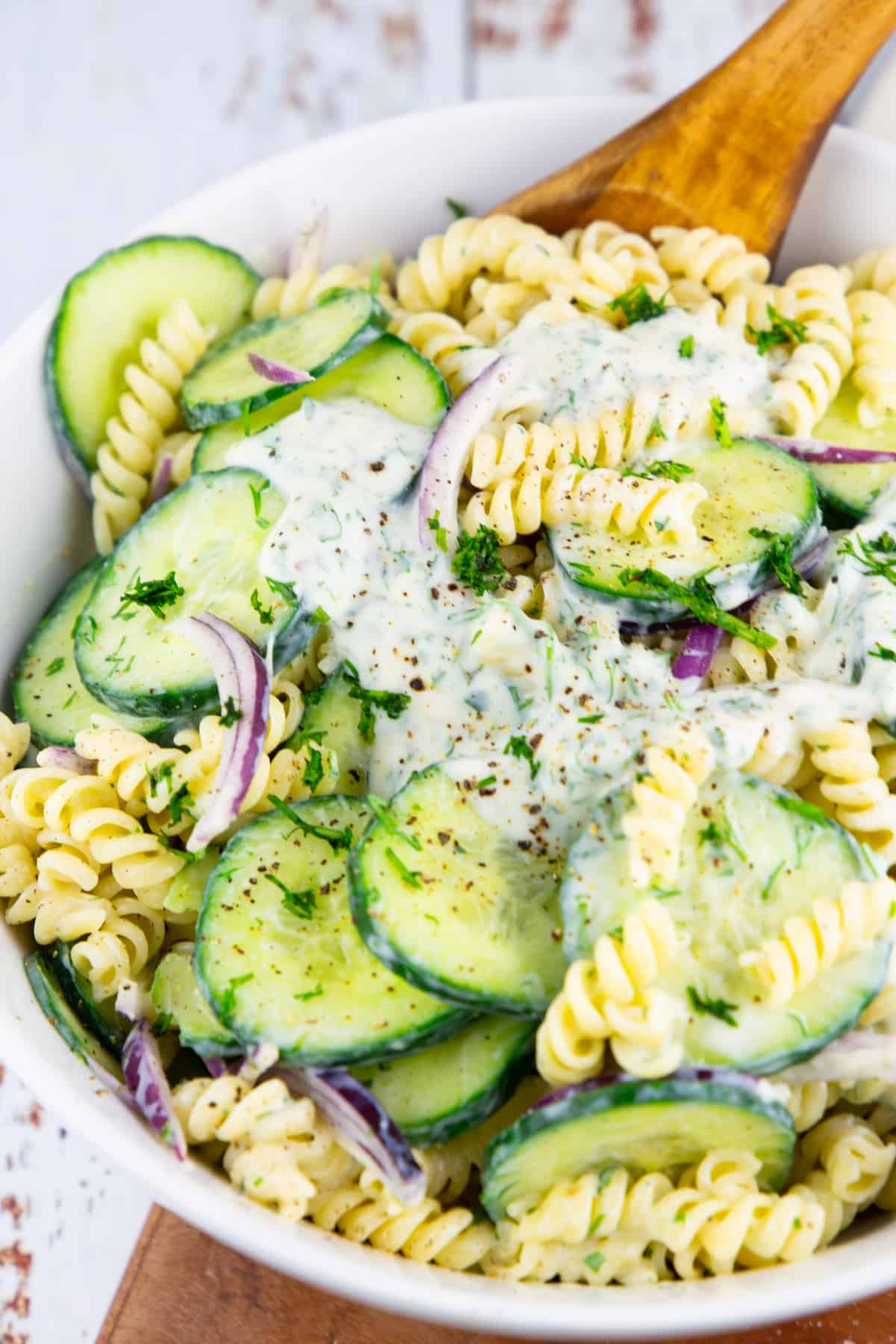 close-up of a cucumber pasta salad in a white bowl on a wooden board