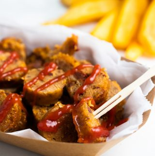 a sliced vegan sausage on a paper plate with fries in the background