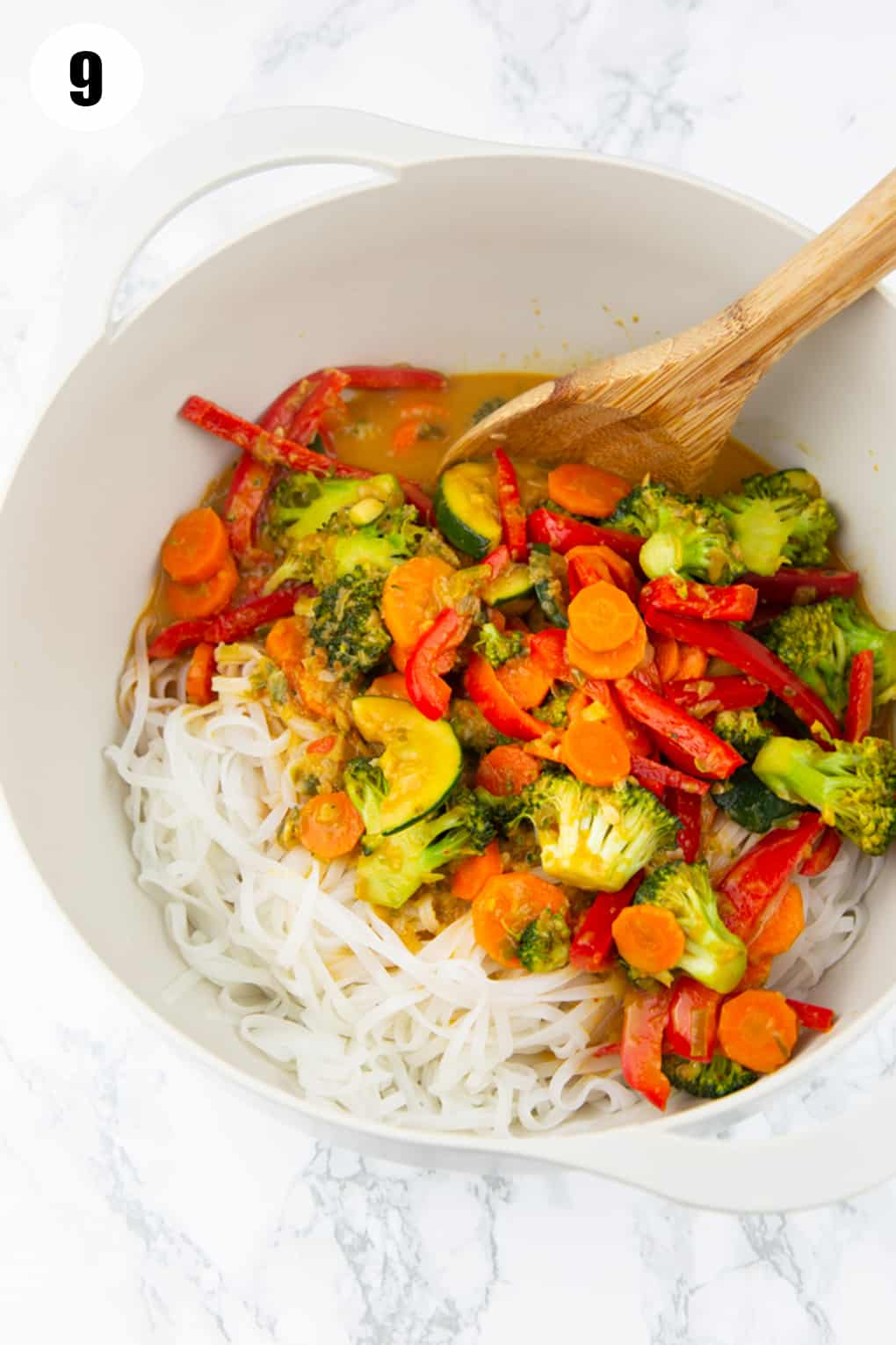 sautéed vegetables and rice noodles on a large bowl with a wooden spoon on a marble countertop
