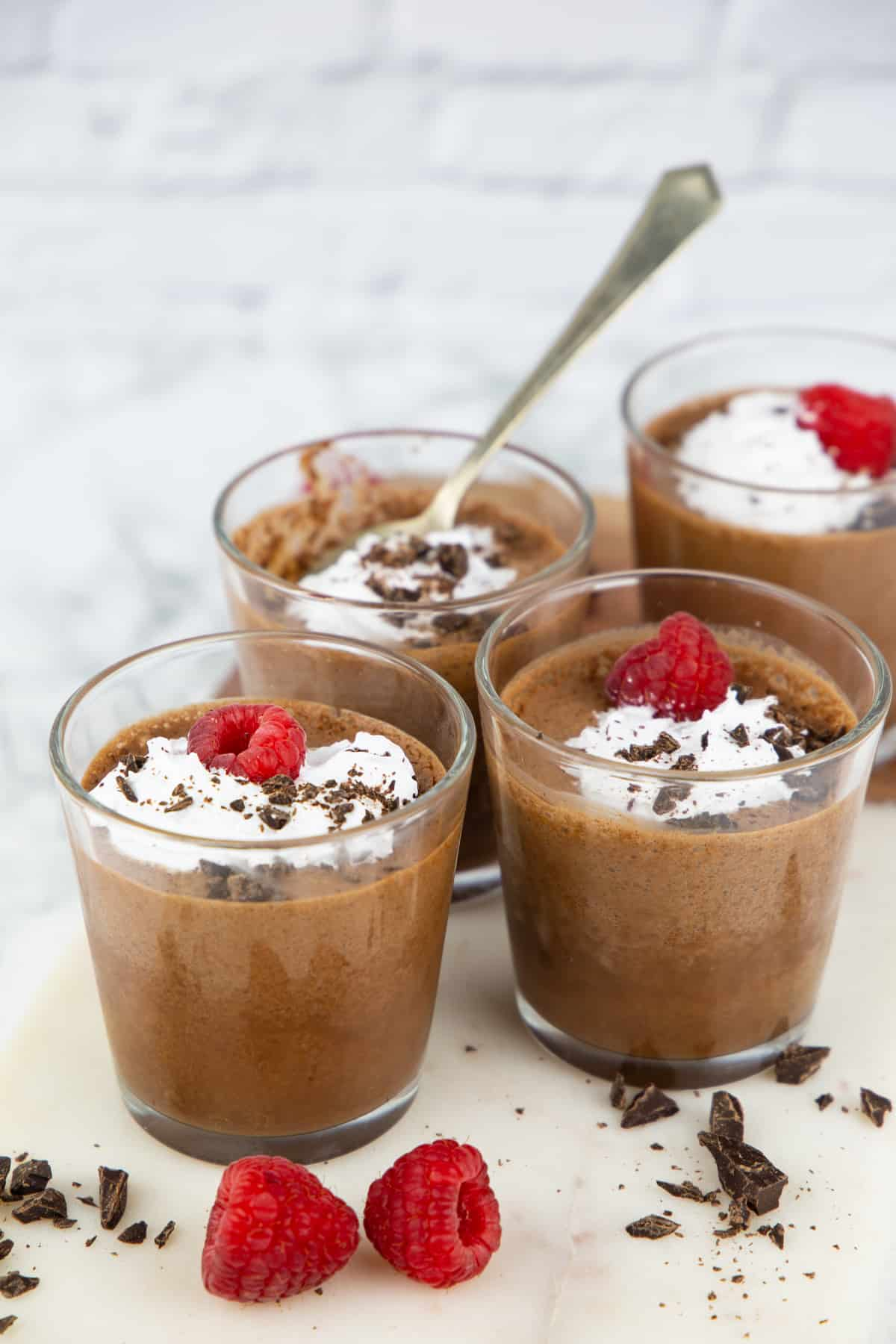 four glasses with aquafaba chocolate mousse on a marble board with raspberries on the side