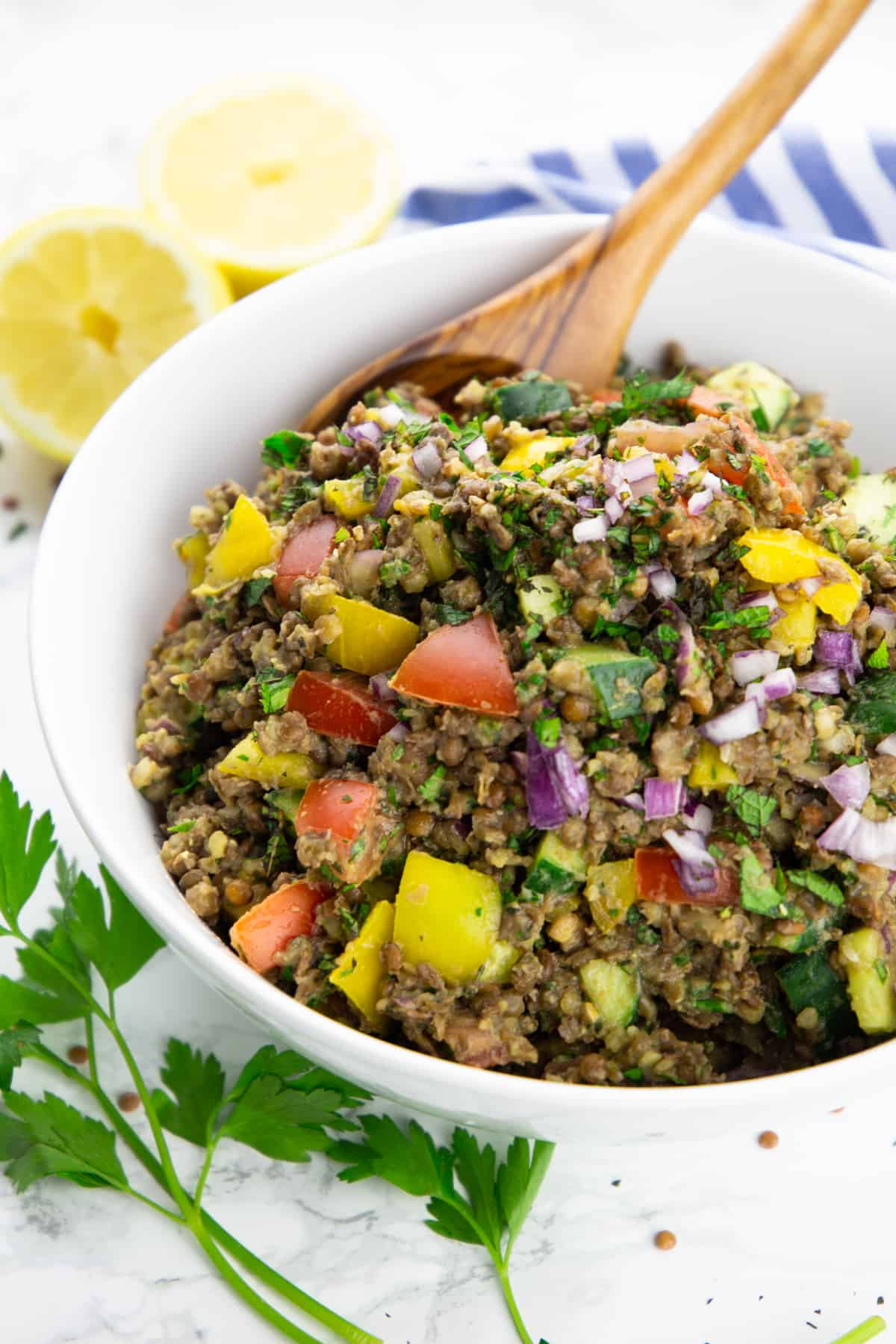 lentil salad with tomatoes, cucumber, and bell pepper in a white bowl with a wooden spoon