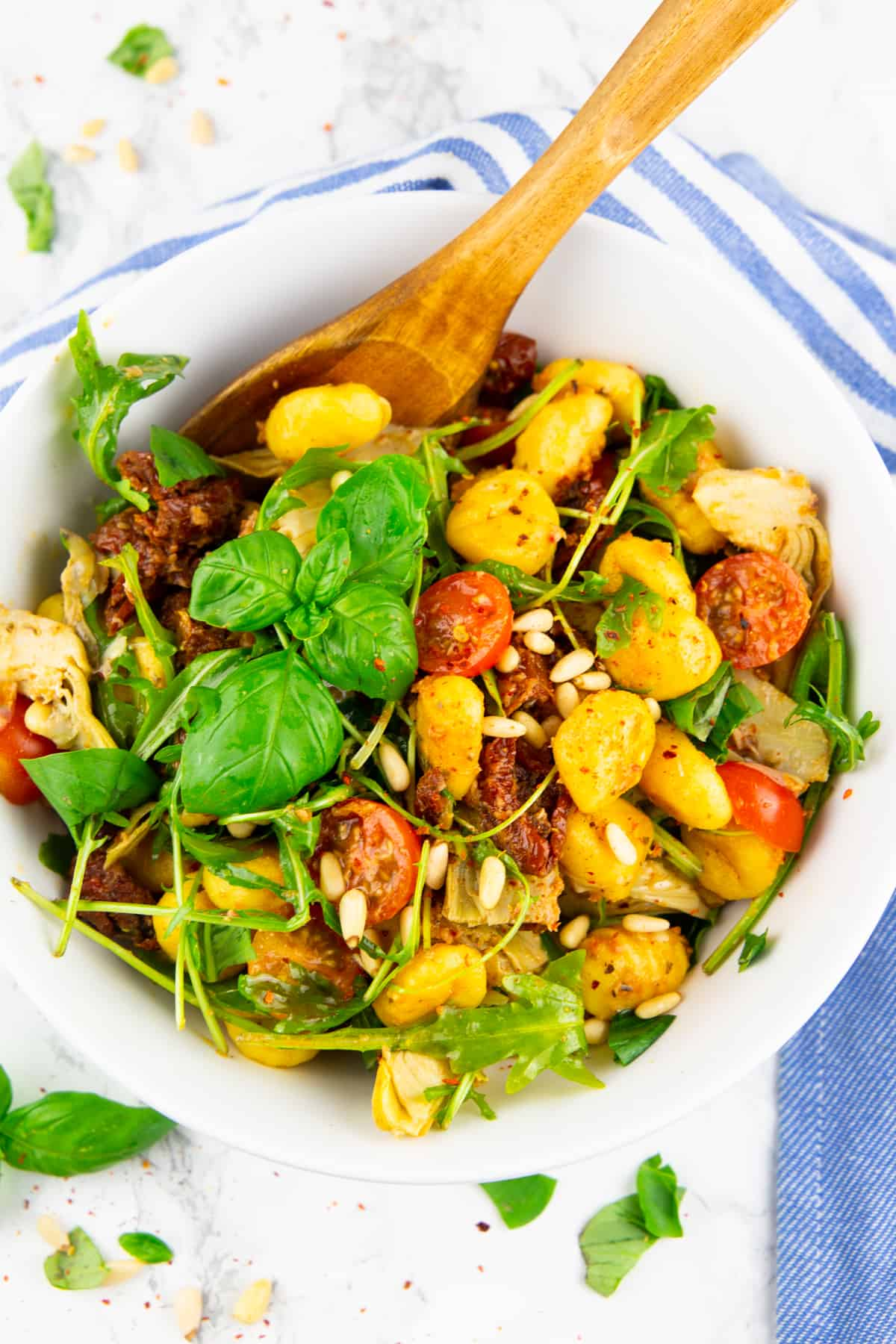pesto gnocchi with tomatoes, artichokes, and arugula in a white bowl with a wooden spoon