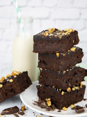 a stack of four zucchini brownies on a white plate with a bottle of milk in the background