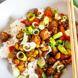 Kung Pao Tofu over rice in a white plate with chop sticks