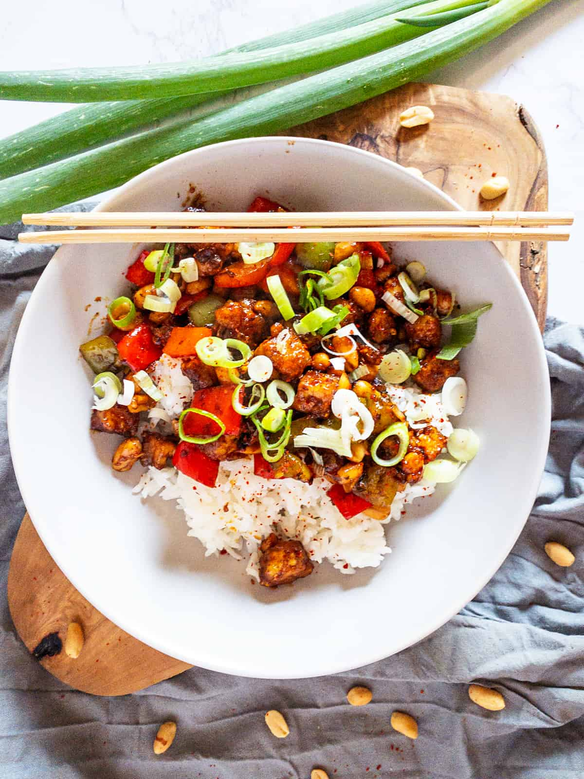 Kung Pao Tofu with white rice in a white bowl with green onions and peanuts on the side