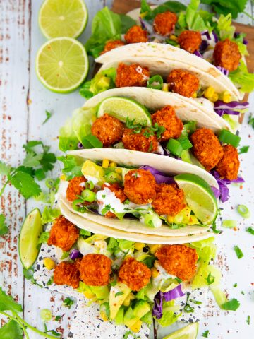 tacos filled with baked tofu cubes, lettuce, and avocado on a wooden board with limes on the side