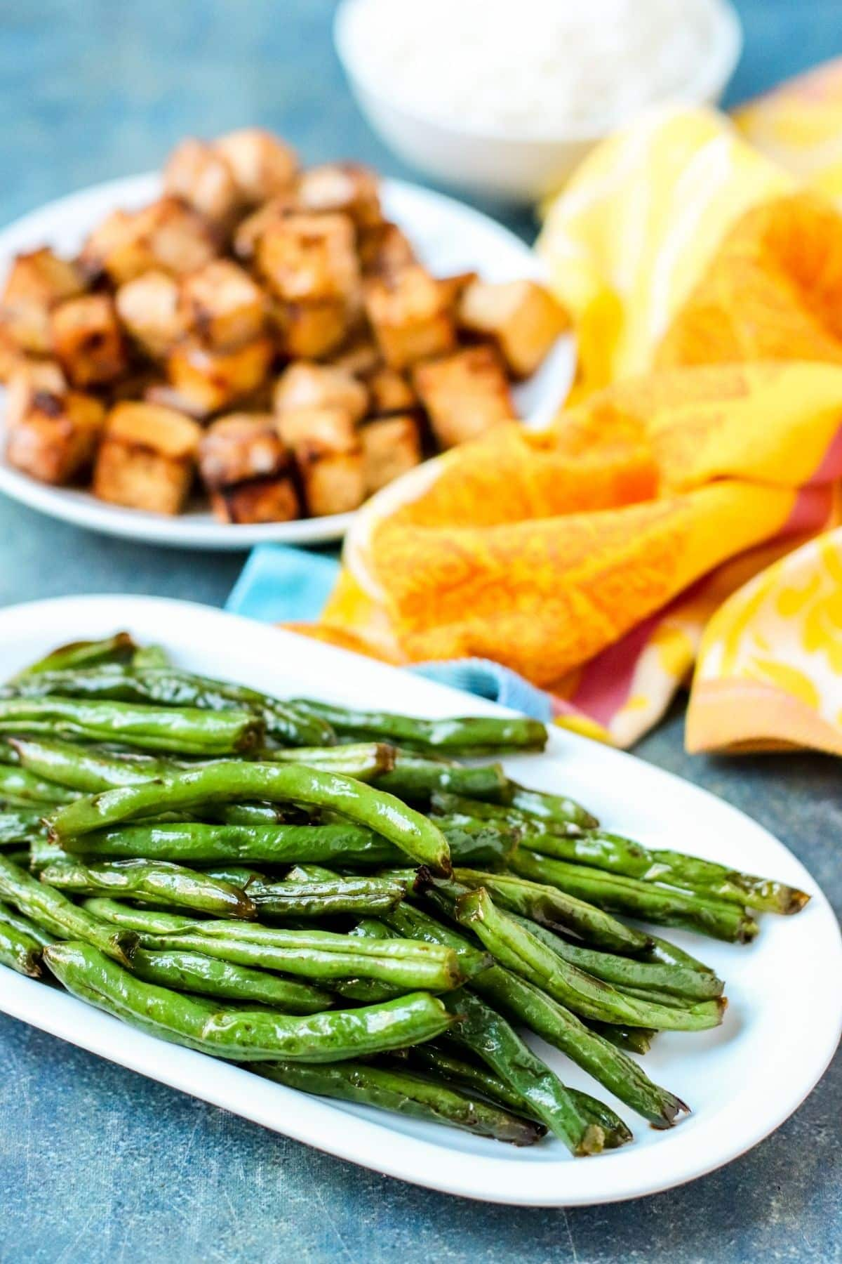 air fryer green beans on a white plate with another plate with tofu cubes in the background