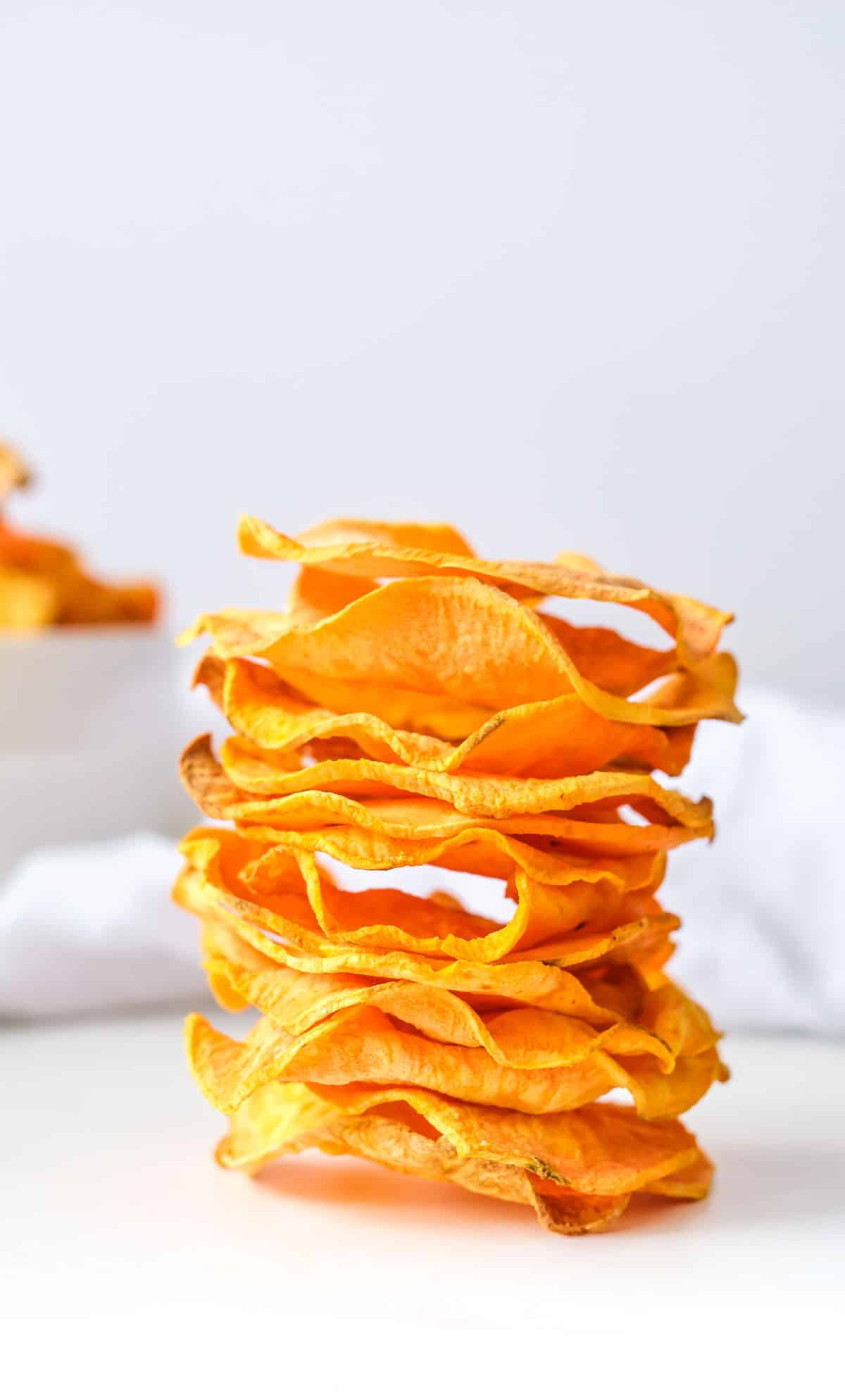 a stack of air fryer sweet potato chips on a white countertop