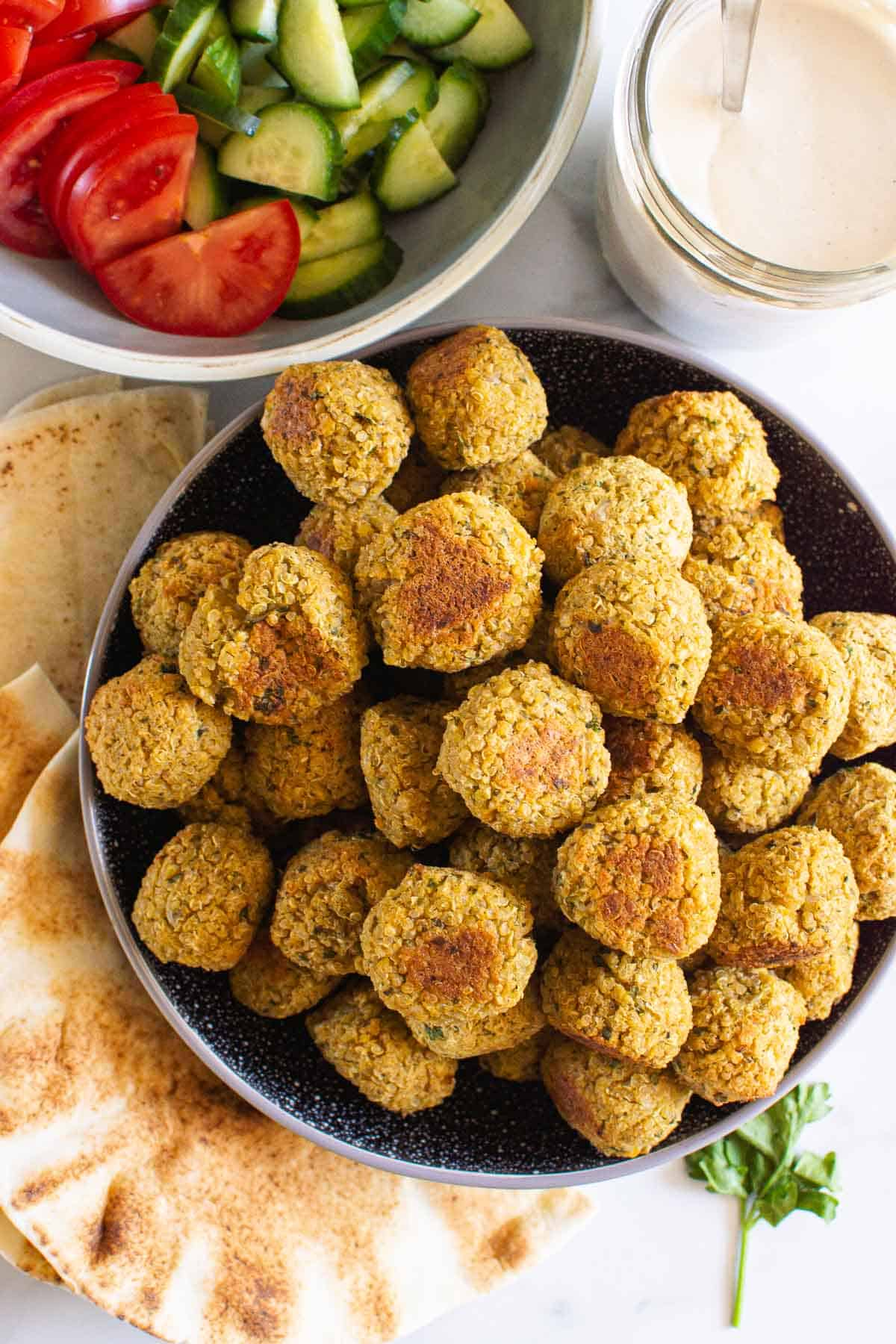 a bowl with quinoa falafel with another bowl with cucumber and tomatoes in the background