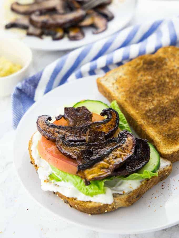 a vegan sandwich with mushroom bacon on a white plate